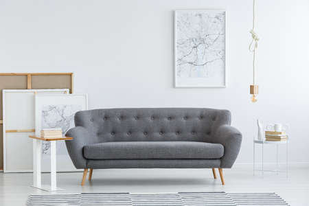 Simple, artistic living room interior with a white map poster hanging above a gray sofa 스톡 콘텐츠