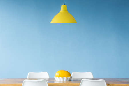 Minimal style, symmetric interior with a yellow lamp hanging over a wooden table with a melon in a dish standing on it as well as visible tops of chairs around it 스톡 콘텐츠