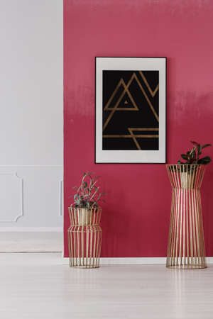 Modern poster with triangles hanging on red wall in lobby interior with golden plant pots Foto de archivo