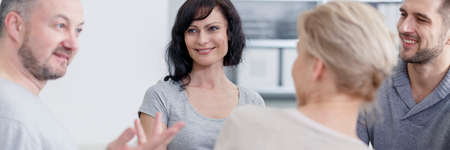 Smiling people talking with psychologist during group therapy Stockfoto