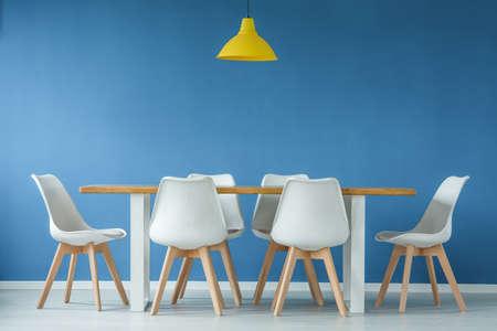 Modernas sillas blancas y de madera alrededor de una mesa de comedor y una lámpara amarilla contra la pared de fondo azul en un interior de estilo minimalista.