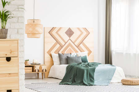 Green bedding on bed against wooden geometric board in natural bedroom interior with rattan lamp