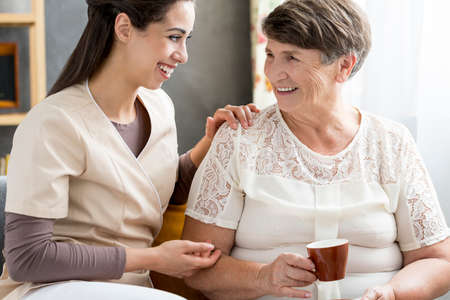 Beautiful volunteer talking cheerfully to a senior patient who is drinking tea Фото со стока