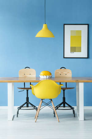 Minimal style symmetric interior with a yellow lamp hanging over a wooden table with a melon in a dish, chairs and a poster on a blue wall Stock Photo