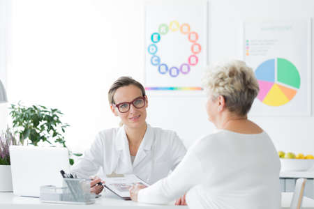 Doctor planning a weight loss diet plan together with her elderly patient trying to eat healthy