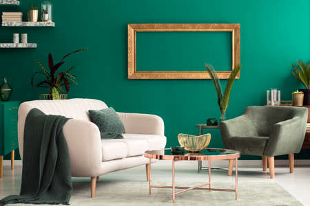 Copper table between beige settee and armchair in green living room interior with empty, gold frame