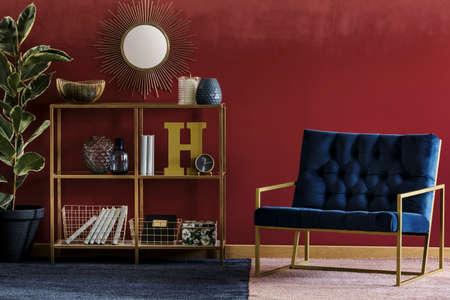 해군 블루 안락 의자와 화분 부르고뉴 룸 인테리어에 서와 장식 서 황금 금속 랙