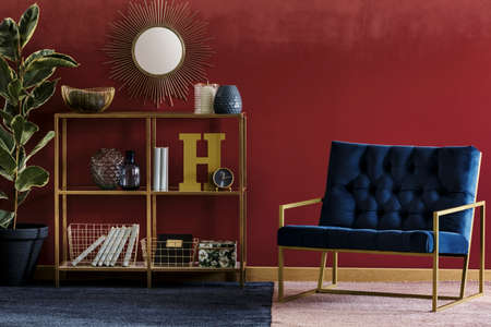 Golden metal rack with books and decor standing in burgundy room interior with navy blue armchair and potted plant Foto de archivo
