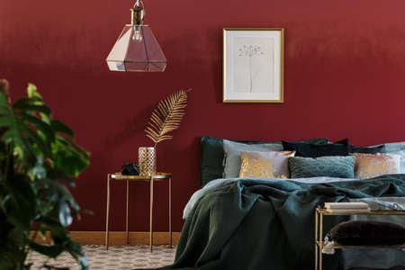 Affiche simple accrochée au-dessus du lit avec de nombreux coussins et couverture verte debout dans l'intérieur de la chambre avec des meubles dorés