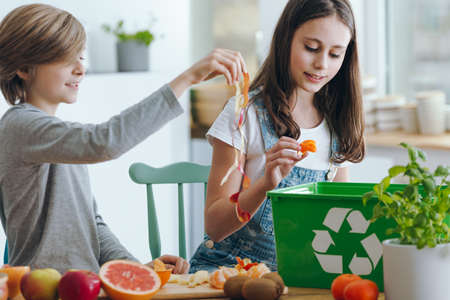 Girl and boy trowing out fruits waste into green recycling container