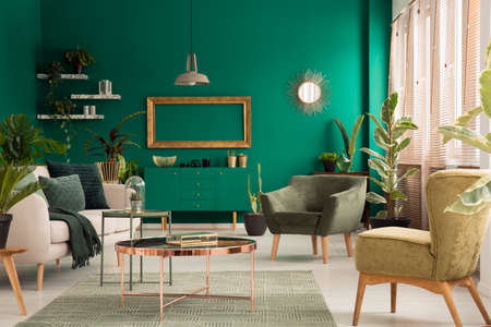 Copper table on rug between beige sofa and armchair in green, spacious living room interior with mockup