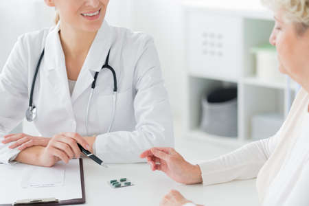 Close-up of a doctor wearing a white coat and stethoscope prescribing medication and supplements to a senior patient