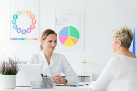Doctor at an appointment looking happy with her elderly patients weight loss progress Stock Photo