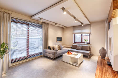 Spacious, brown living room interior design with sofa, table, lighting, large sliding balcony window and curtains