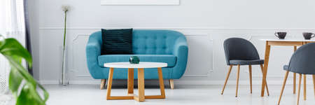 Blue sofa with decorative pillow and white coffee table with glass candle holder in living room interior Stockfoto