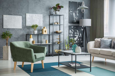 Green armchair standing next to a metal table with marble pattern placed in industrial living room interior with plants and decor