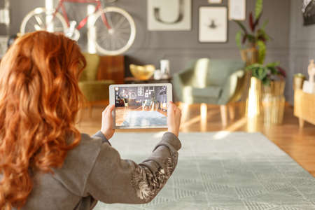 Ginger girl taking a photo of a living room interior with a tablet for her blog