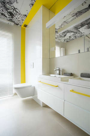 Trendy, modern, white bathroom interior design with creative yellow elements