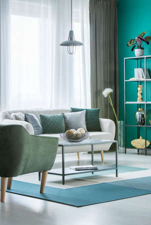 Metal marble table with decorative balls in bowl in green living room interior with light grey sofa and windows with curtains Stock Photo