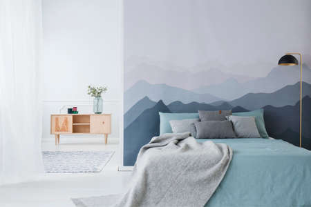 Blue bed with grey blanket against mountain wallpaper in simple bedroom interior with wooden cupboard
