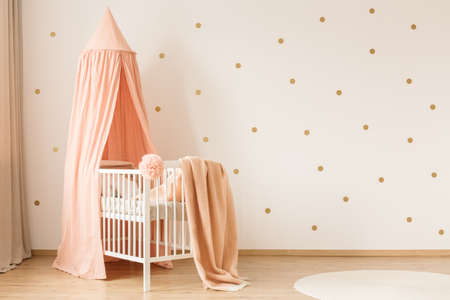 Pink blanket on white crib against wallpaper with gold dots in kids bedroom interior
