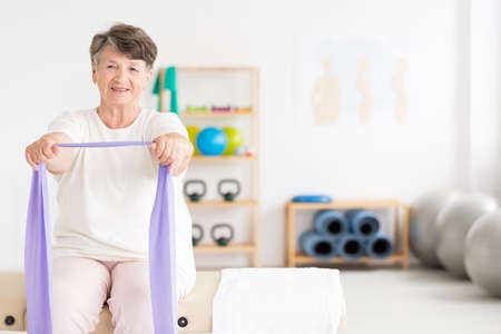 Smiling, active old woman exercising at a gym using fitness equipment