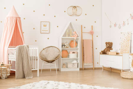 Gold armchair and ladder in pastel girly bedroom interior with canopied white crib
