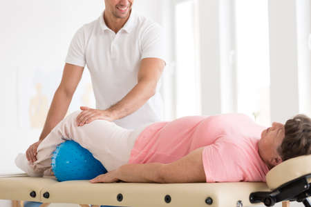 Smiling therapist massaging an old woman with osteoporosis using a blue ball