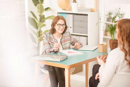 Uśmiechnięty osobisty doradca rozmawia z klientem w jej jasnym, przytulnym biurze