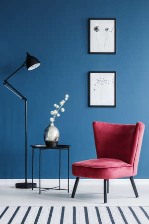 Red chair next to table with flowers and lamp in blue living room interior with posters