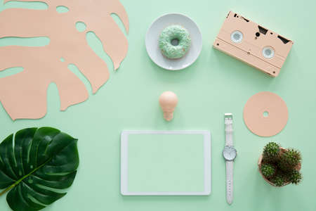 Mockup on tablet on mint background with pink leaf, cassette and doughnut