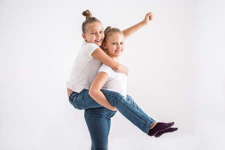 Portrait of a young, happy girl having fun, enjoying a piggyback ride on her sisters back against a white background 版權商用圖片