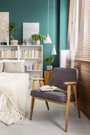 Close-up of a gray armchair with a book on it in cozy, white bedroom interior with bookcases behind the bed 写真素材