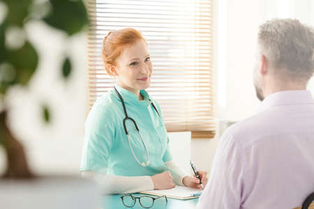 Beautiful nurse talking to a male patient in a medical clinic