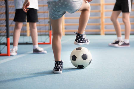 Close-up of boys' legs wearing sneakers while playing football in the playground Stock Photo