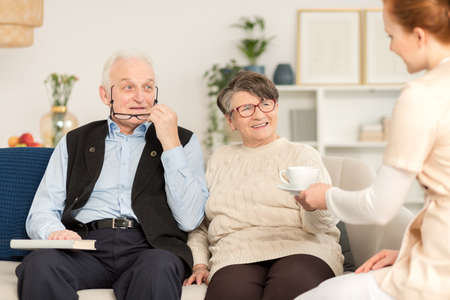 Elderly couple having a tea with a nurse during a home visit