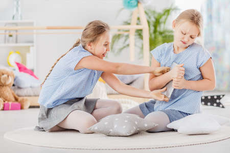 Girl trying to grab a tablet from her twin sister who does not want to share Stock Photo