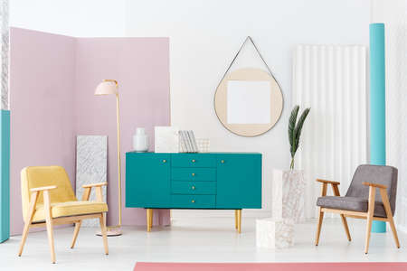 Stylish furniture campaign idea for a modern living room interior with pastel colors, turquoise blue scandinavian style sideboard and elegant decorations Stock Photo