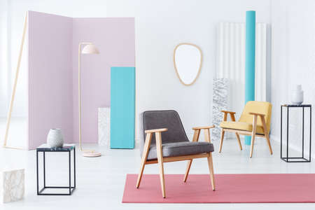 Modern furniture and accessories still life composition in a fun bright interior with pink, blue and marble elements and armchairs