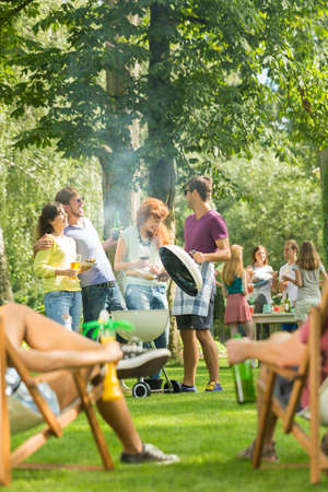 Grill party held in a park by a large group of friends enjoying the warm weather and food 스톡 콘텐츠
