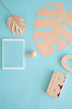 Mockup on tablet on pastel blue background with peach leaves and cassette 版權商用圖片