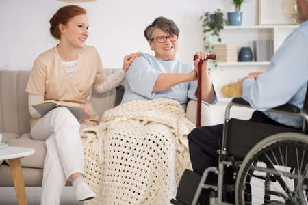Beautiful nurse spending time with a disabled senior couple in a nursing home Banque d'images - 99889867