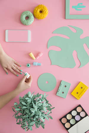 Woman painting nails on pink desk with yellow doughnut, mint leaf and mockup of smartphone. Beauty blogger concept