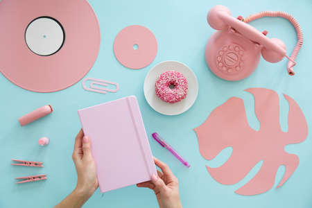 High angle of freelancer with pink notebook. Leaf, phone, vinyl and doughnut on blue desk