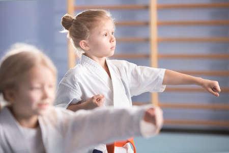 Young girl in kimono exercising during an extra-curricular karate class 免版税图像
