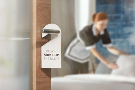 A housemaid cleaning a room in the background and door with a sign at the front