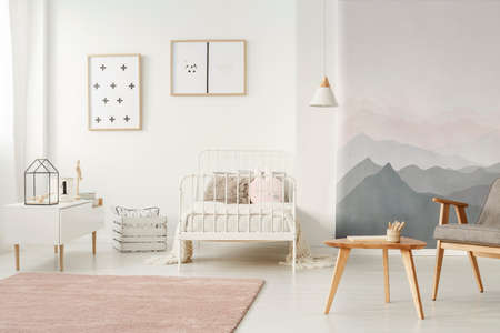 White, metal bed standing in bright kids room interior with simple posters, dirty pink carpet and mountain wallpaper