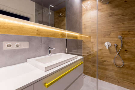 Interior of wood and marble bathroom with glass shower door, stainless steel shower head and white cupboards Stock Photo