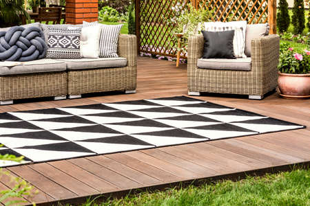 Black and white geometric carpet on wooden veranda with rattan furniture Stock fotó