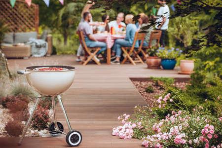 Grill con salchichas en el jardín con flores y grupo de amigos celebrando en el fondo Foto de archivo
